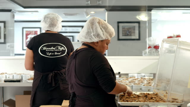 ws pan across toffee shop packaging tables as workers stuff toffee bark into cans and seal shrink wrap on cans with heat gun / rancho mirage, california, usa - toffee stock videos & royalty-free footage