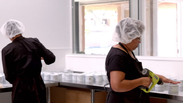 vidéos et rushes de ws pan across toffee shop packing area as workers put finishing touches on toffee cans and gift boxes with heat gun sealing shrink wrap and red ribbons tied around boxes of toffee / rancho mirage, california, usa - charlotte médicale ou sanitaire