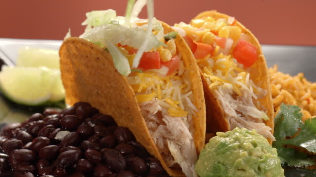cu pan across two tacos on dinner plate with rice and beans, filled with shredded chicken, cheese, pico de gallo as lettuce shreds are sprinkled on top - taco stock videos & royalty-free footage