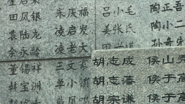 cu pan across wall of names outside memorial hall of nanjing massacre / nanjing, jiangsu, china - 大量殺人点の映像素材/bロール