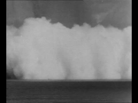 vídeos de stock e filmes b-roll de ws across water as cloud from atomic bomb explosion at bikini atoll engulfs battleship uss arkansas in front of it / aerial one of the target ships... - atol de biquini