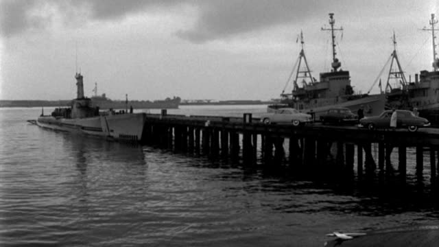 dx - across water toward submarine tied up at deck - san diego harbor b.g. - b&w.  (nit. neg) - herumfahren stock-videos und b-roll-filmmaterial