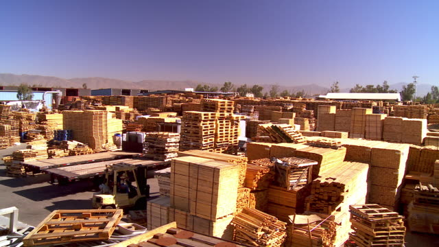 WS PAN across wooden pallet manufacturing and repair and pallet storage facility covering entire city block / Fontana, California, USA