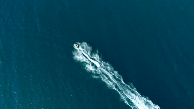 action aerial shot of a drone following a jet in the sea water - pursuit concept stock videos and b-roll footage