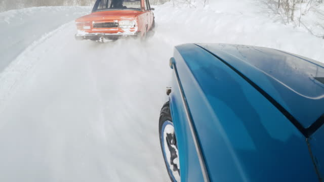 Action camera shot of speeding car drifting on snowbound road