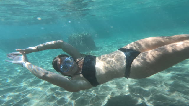 action camera view underwater of female swimming in bikini - diving flipper stock videos & royalty-free footage