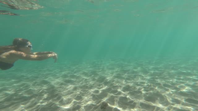 stockvideo's en b-roll-footage met actie cameraweergave onderwater van vrouwelijke zwemmen in bikini - zwemvlies
