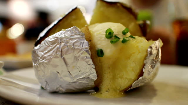 action :grilled foil-wrapped potatoes - butter stock videos and b-roll footage