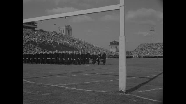 action on field, crowd in stands in municipal stadium for football game between army and navy / navy midshipmen march onto field / another view of... - 士官候補生点の映像素材/bロール
