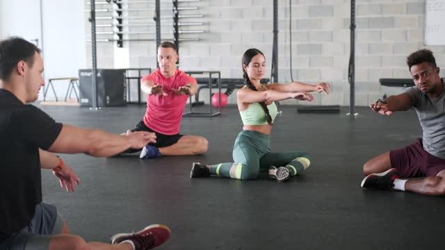 vídeos y material grabado en eventos de stock de retrato de acción del entrenador y los atletas que hacen estiramiento de hombro - articulación humana