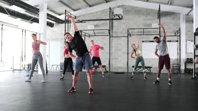 vídeos y material grabado en eventos de stock de retrato de acción del entrenador y los atletas que hacen estiramiento de hombro - entrenamiento sin material