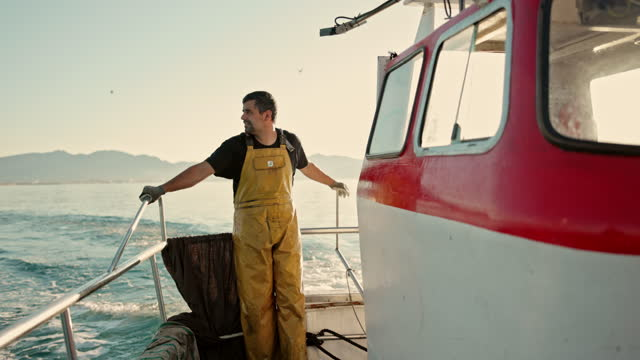 action portrait of fisherman motoring on small trawler - fisherman stock videos & royalty-free footage