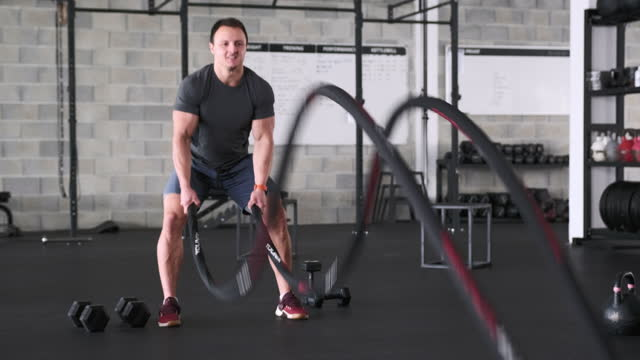 action portrait of sportsman working out with battle ropes - rope stock videos & royalty-free footage
