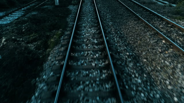 Action shot of a video drone flying low over railroad train tracks