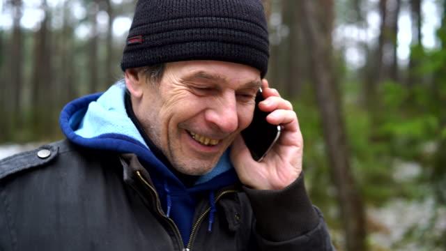 stockvideo's en b-roll-footage met actieve 70-jaar-oud senior man praten via cellphone whem hij wandelen in het woud van de winter - 70 79 jaar