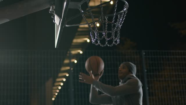 aktive sportler ball in den basketballkorb zu werfen - basketball stock-videos und b-roll-filmmaterial