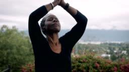 Active baby boomer African American woman exercising yoga sun salutation poses