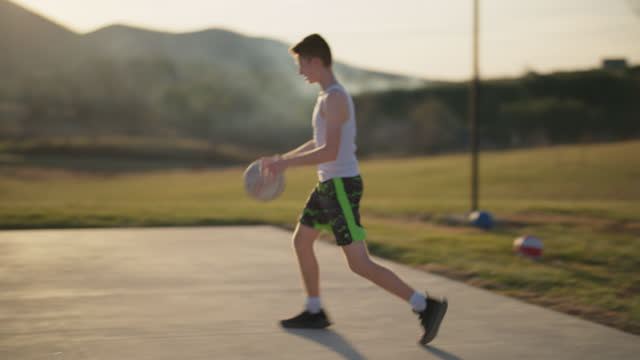 active boy dribbles and plays with basketball and successfully shoots basket - one teenage boy only stock videos & royalty-free footage