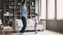 Active cheerful dad dancing having fun with kid at home