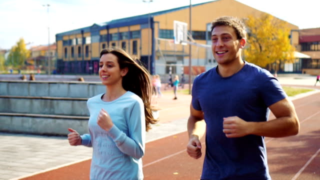 Active couple jogging on athletic track