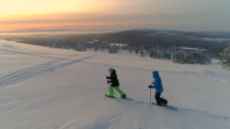 AERIAL Active couple snowshoeing up a mountain slope in snowy Lapland at sunrise