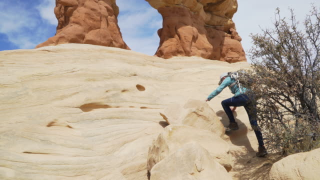 active elderly lady backpacking outdoors and hiking up rock formation - sandstone stock videos & royalty-free footage