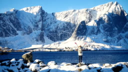 active girl enjoying beautiful view of winter Lofoten archipelago landscapes with snowed mountains and nothern sea