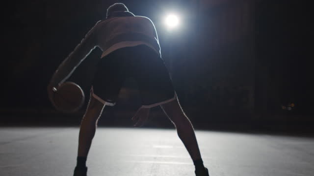 Active male athlete dribbling basketball at night