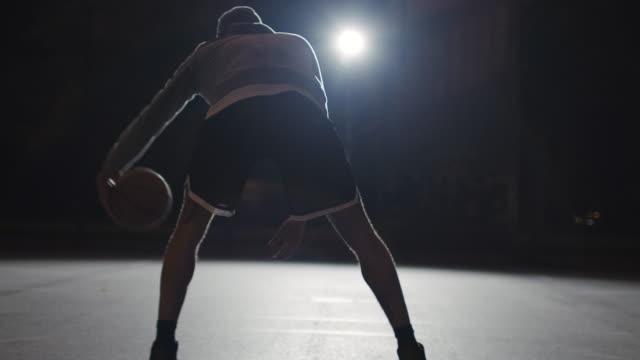 vídeos de stock e filmes b-roll de active male athlete dribbling basketball at night - fintar desporto
