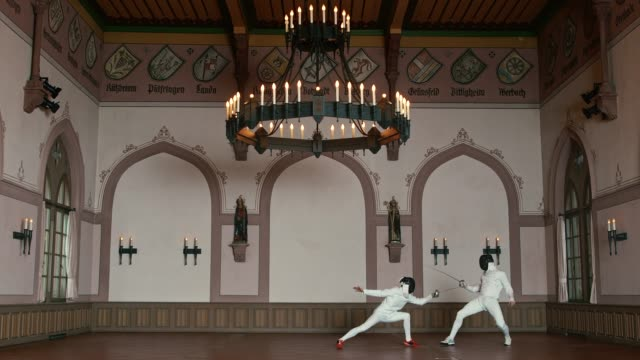 Active male fencers dueling in castle