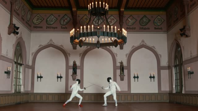 Active male fencers fighting in historical castle
