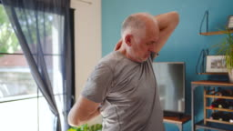 Active mature man doing arm stretching exercises at home