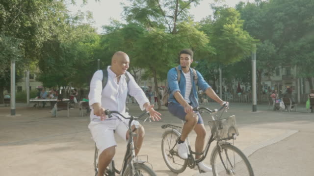 active mixed race men cycling on city break in barcelona - modern manhood stock videos & royalty-free footage