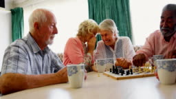 Active mixed-race senior people playing chess game in the nursing home 4k