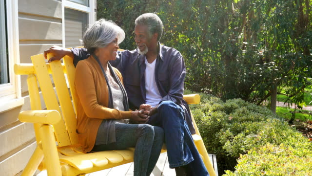 Active Senior African American Couple Enjoying Time Sitting Together Outside