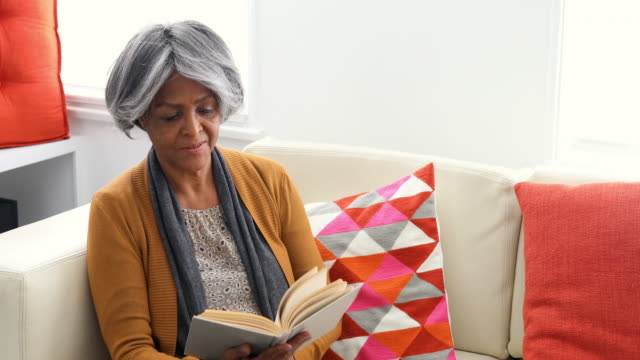 Active Senior African American Woman Reading on the Sofa