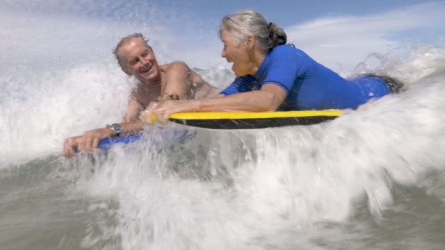 stockvideo's en b-roll-footage met active senior couple bodyboarding together at the beach - actieve ouderen