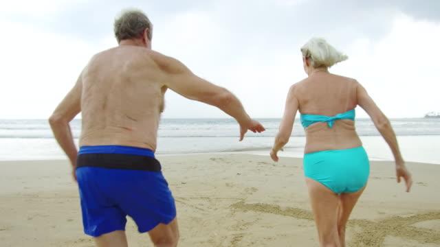 vídeos y material grabado en eventos de stock de pareja senior activo en la playa en traje de baño corriendo hacia el mar - traje de baño