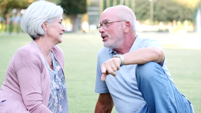 vidéos et rushes de couple de personnes âgées actives vous détendre sur la pelouse dans le parc de la ville - jeune d'esprit
