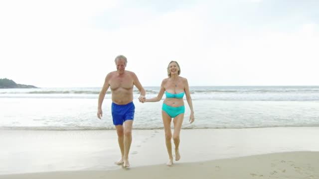 vidéos et rushes de couple de personnes âgées actives allant de mer vers la caméra sur la plage de sable fin - bikini