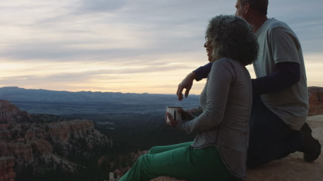 vídeos de stock e filmes b-roll de 4k uhd: active senior couple soaking in bryce canyon sunrise - parque natural