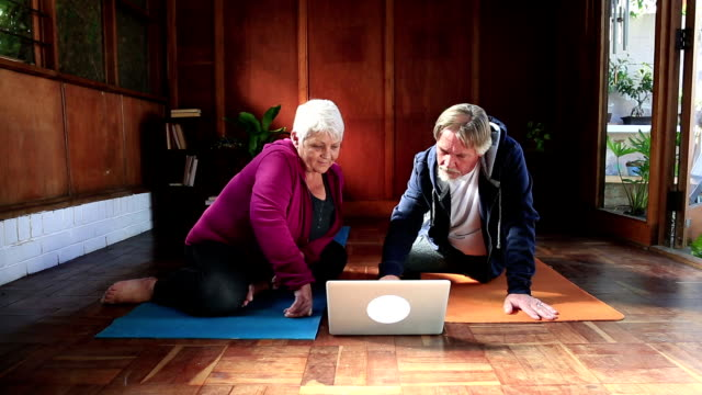 Active senior couple watch exercise video on laptop