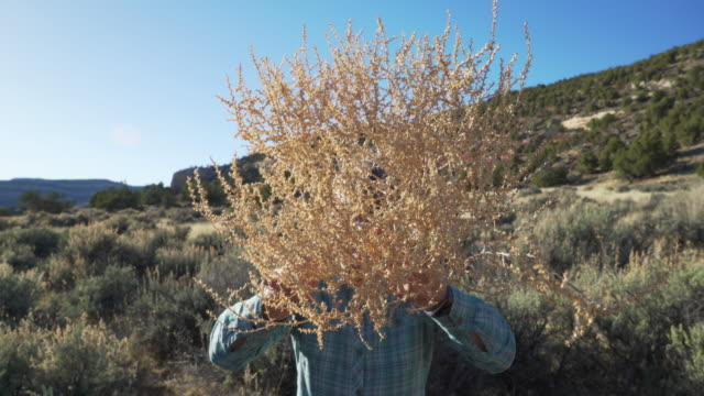 Active senior female with tumbleweed head standing in sandstone canyon Utah