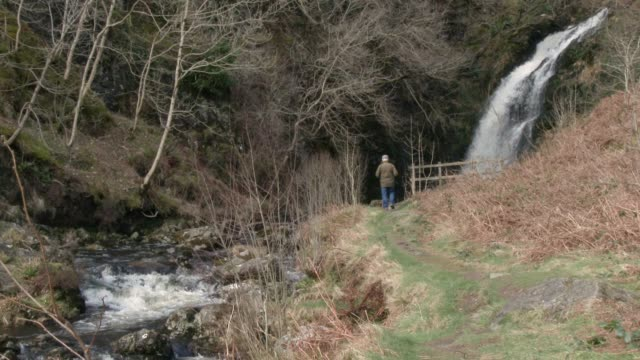 Active senior man at a waterfall in Scottish countryside