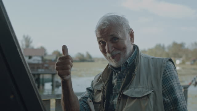 active senior man showing thumbs up - standing water yard stock videos & royalty-free footage