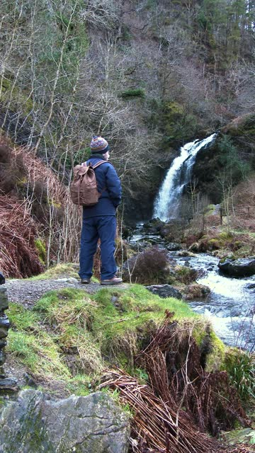 active senior man stopping to look at a waterfall - johnfscott stock videos & royalty-free footage