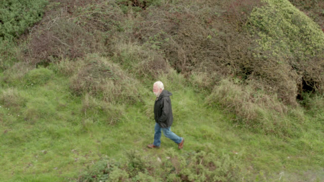 active senior man walking along a coastal path in dumfries and galloway - galloway scotland stock videos & royalty-free footage