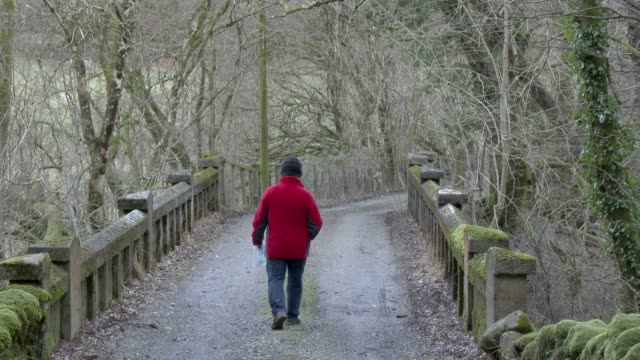 Active senior man walking away from camera carrying a map