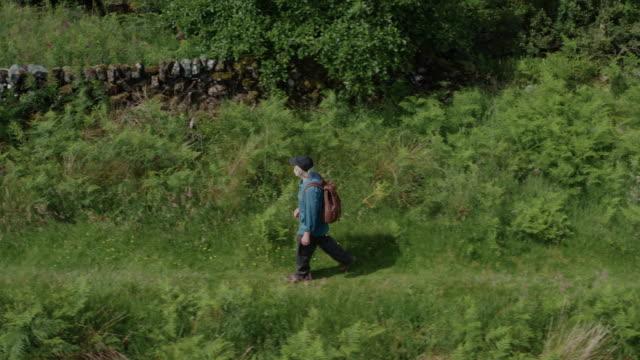 vidéos et rushes de homme aîné actif marchant à côté d'une petite rivière lente coulant dans un sud-ouest rural éloigné de l'ecosse - remote location