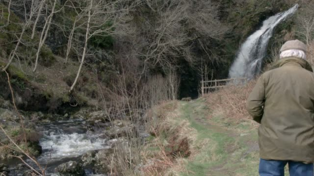 Active senior man walking towards a waterfall in Scottish countryside